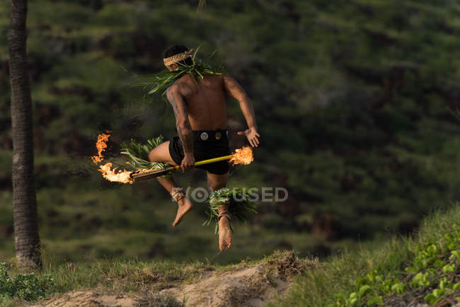 Male fire dancer performing with fire levi sticks at beach — Stock Photo