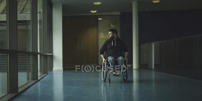 Hombre discapacitado en silla de ruedas moviéndose de paso en el gimnasio - foto de stock