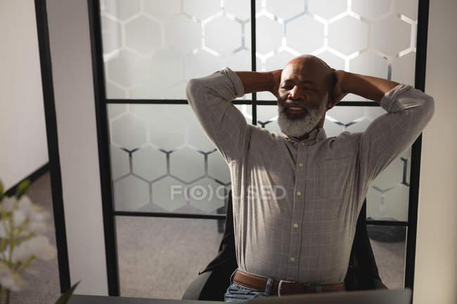 Старший дизайнер расслабляющий с руками за голову в офисе — стоковое фото