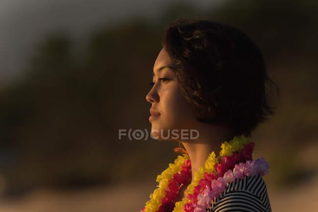 Красивая женщина в гирлянде стоит на пляже — стоковое фото
