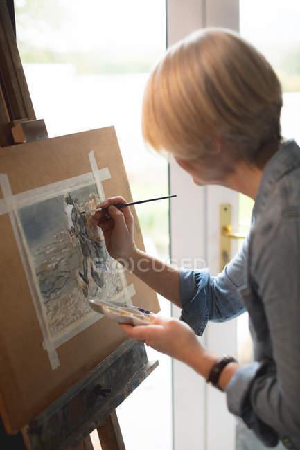 Artista feminina pintura imagem na lona em casa — Fotografia de Stock
