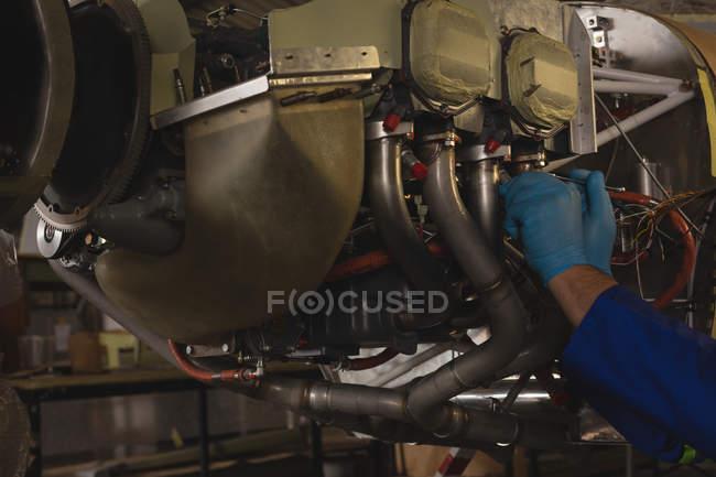Primer plano del ingeniero reparando el motor de la aeronave en el hangar - foto de stock