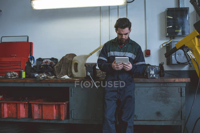 Mechanic using digital tablet in repair garage — Stock Photo