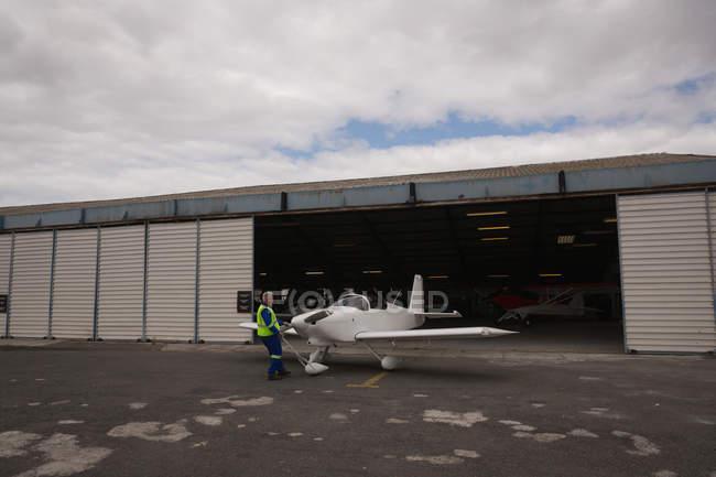 Vue arrière du membre de l'équipage sortant de l'avion du hangar — Photo de stock