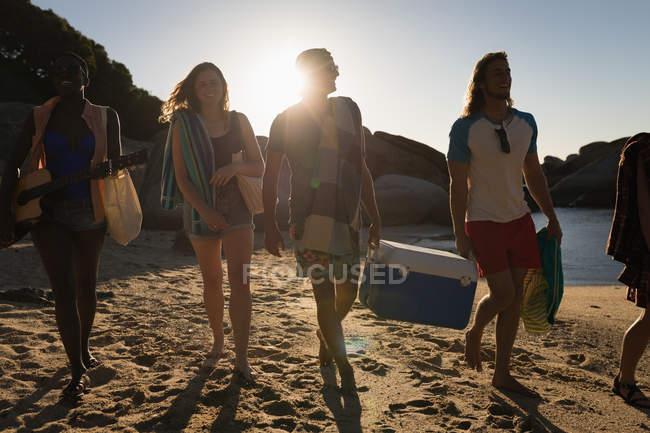 Друзья-мужчины, несущие эски на пляже в солнечный день — стоковое фото