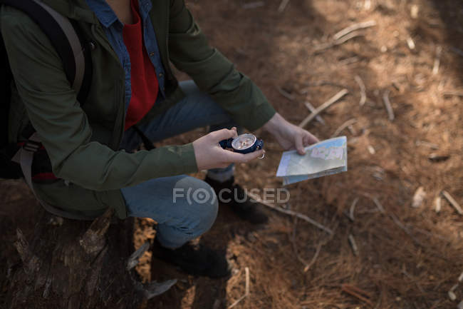 Woman looking compass in forest on a sunny day — Stock Photo