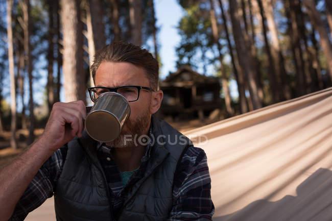 Primo piano dell'uomo che beve il caffè mentre si distende sul hammock — Foto stock