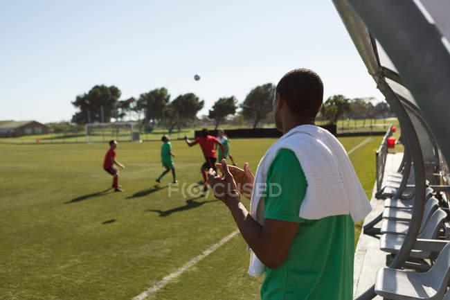 Vista posterior del jugador viendo el fútbol partido de piragua - foto de stock