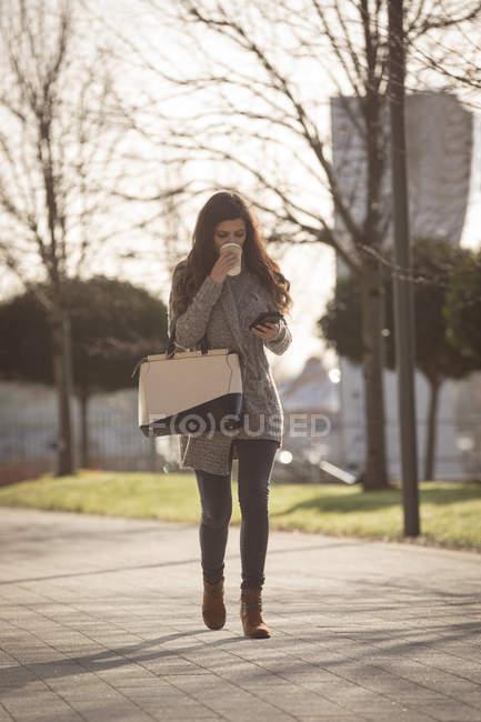 Женщина пьет кофе во время использования мобильного телефона на городской улице — стоковое фото