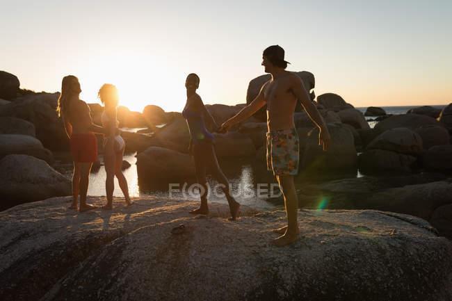 Zwei Paare tanzen in der Abenddämmerung auf einem Felsen am Strand — Stockfoto