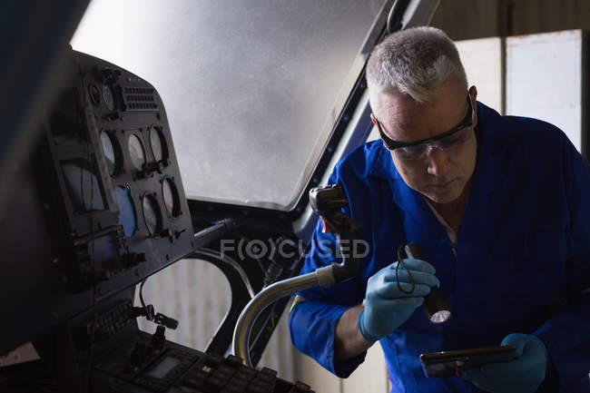 Ingeniero examinando cabina en percha aeroespacial - foto de stock