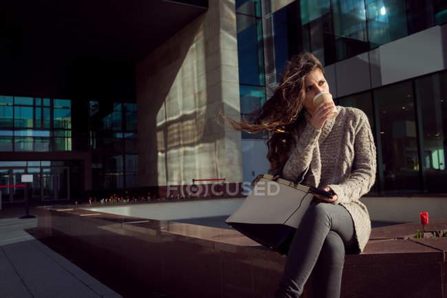Giovane donna che prende un caffè in città — Foto stock