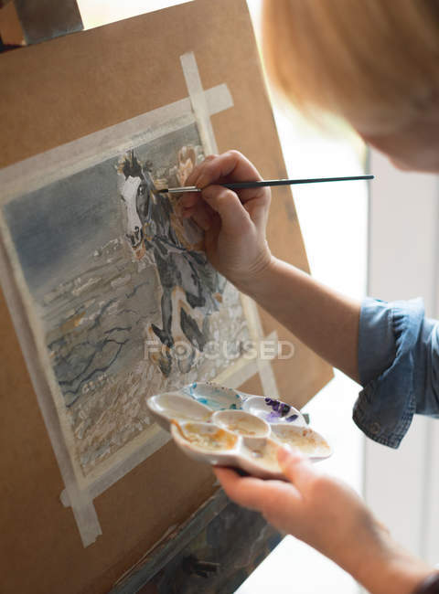 Female artist painting on a canvas with a paintbrush and holding a color palette at home — Stock Photo