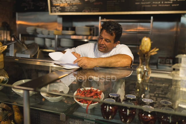 Male baker writing on a notepad at counter in cafe — Stock Photo