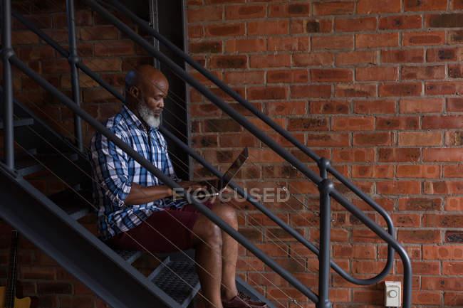 Старший использует ноутбук на лестнице дома — стоковое фото