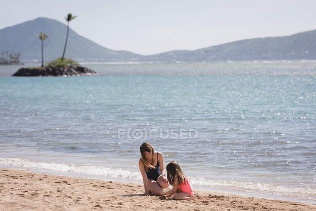 Madre e figlia che giocano nella sabbia in spiaggia — Foto stock