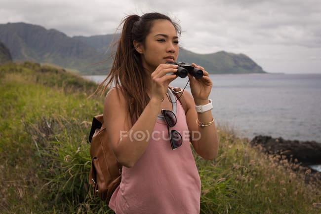 Beautiful woman looking through binoculars in countryside — Stock Photo