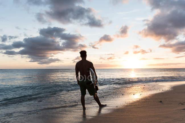 Surfista maschio in piedi con tavola da surf in spiaggia al crepuscolo — Foto stock