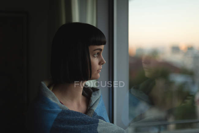 Thoughtful woman looking through window at home — Stock Photo