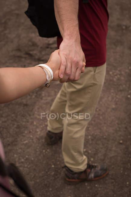 Tenencia de pareja romántica manos en campo - foto de stock