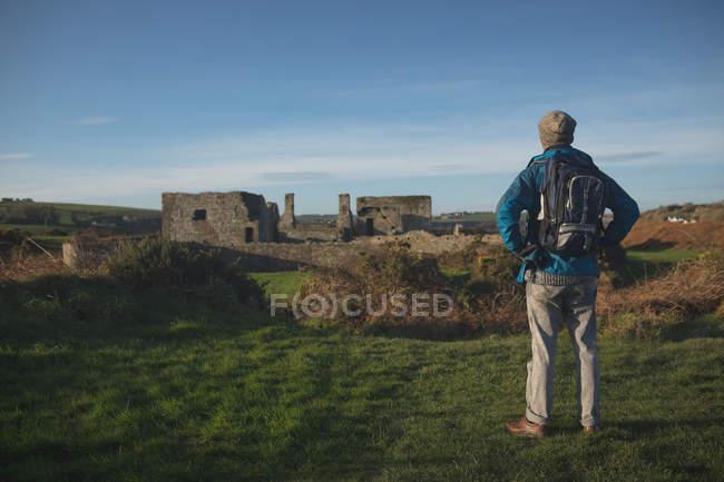 Вид сзади мужчины-туриста, стоящего с рюкзаком в сельской местности — стоковое фото