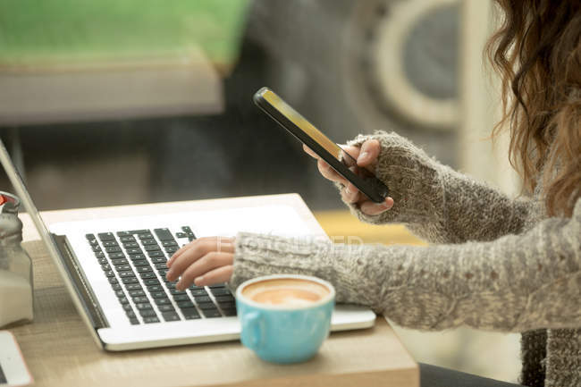 Mid section of woman using laptop and mobile phone in coffee shop — Stock Photo