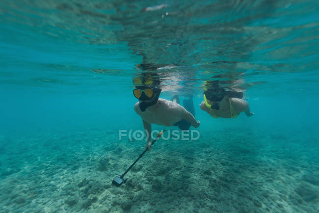 Пара с трубкой под водой в бирюзовое море — стоковое фото