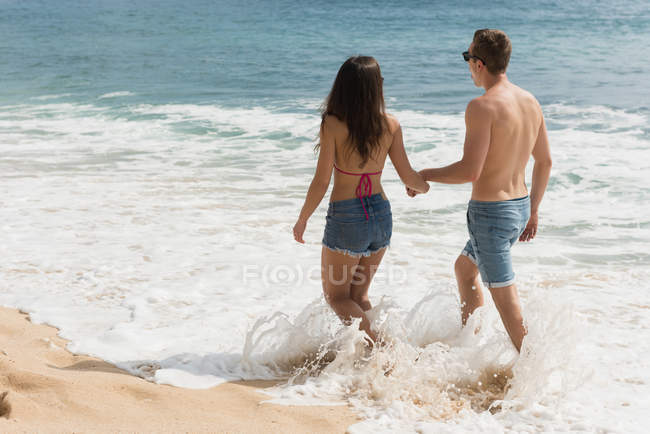 Пара ходьба разом руку на пляжі — стокове фото