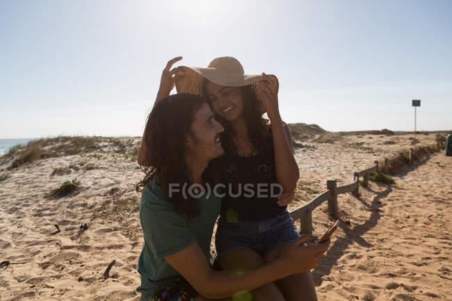Couple s'amuser à la plage par une journée ensoleillée — Photo de stock