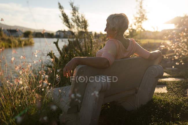 Старші жінки розслабляючий на лавці поблизу Ріверсайд сонячний день — стокове фото
