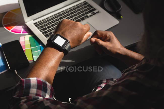 Senior graphic designer checking time on smartwatch in office — Stock Photo