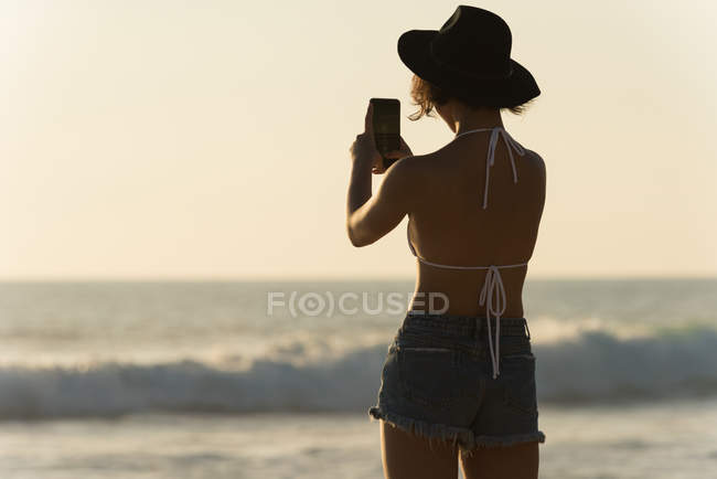 Rear view of woman clicking photos with mobile phone in the beach — Stock Photo