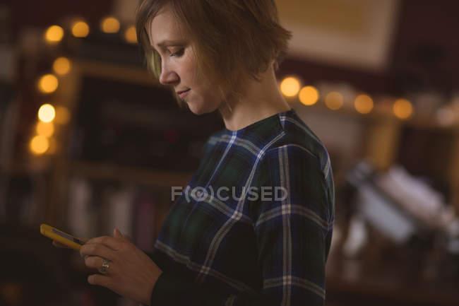 Красивая женщина с помощью мобильного телефона дома — стоковое фото