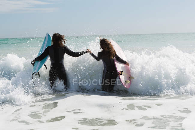 Rear view of surfer couple surfing in the beach — Stock Photo