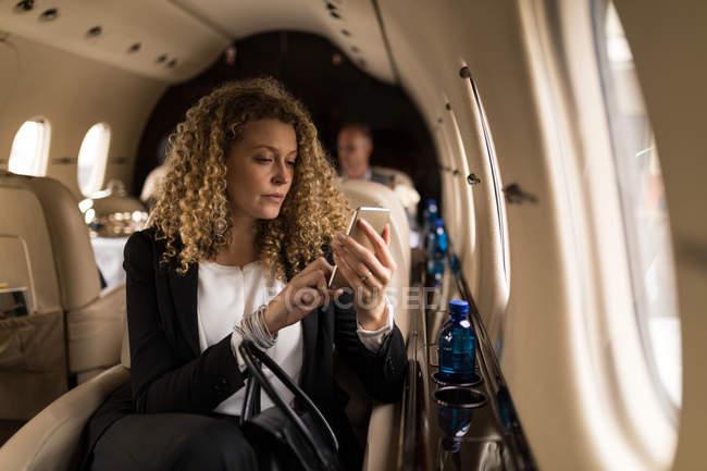 Belle femme d'affaires utilisant le téléphone mobile en jet privé — Photo de stock
