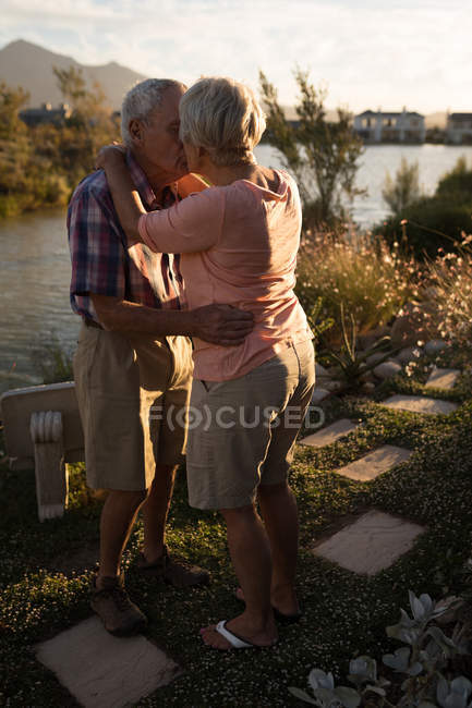 Beautiful senior couple embracing each other near riverside — Stock Photo
