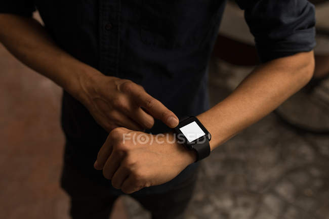 Close-up of businessman using smartwatch in the cafe — Stock Photo