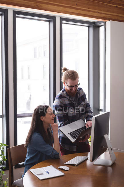 Business colleagues discussing over laptop in office — Stock Photo