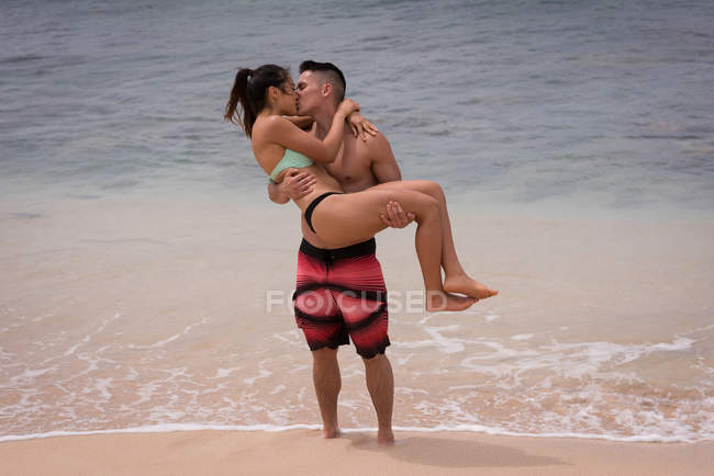 Couple kissing each other in the beach on a sunny day — Stock Photo