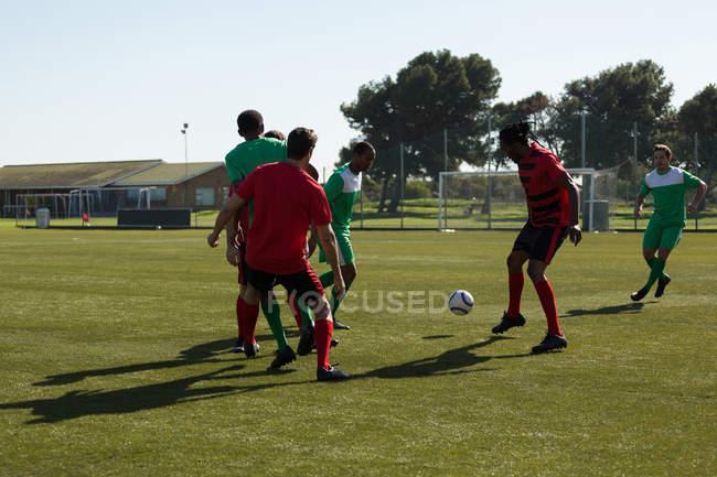 Jugador juego fútbol soccer en el campo de los deportes - foto de stock