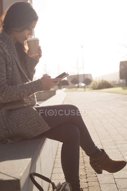 Woman using mobile phone while having coffee on a sunny day — Stock Photo