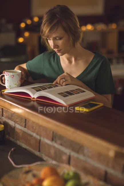 Женщина читает книгу за чашкой кофе дома — стоковое фото