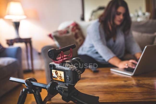 Feminino vlogger sentado no sofá enquanto usando laptop em casa — Fotografia de Stock
