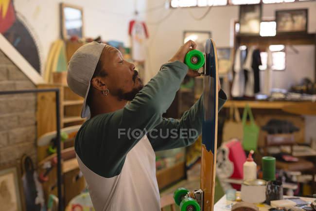 Man making skateboard in workshop — Stock Photo