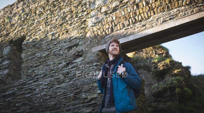Молодой турист, стоящий у старой руины в сельской местности — стоковое фото