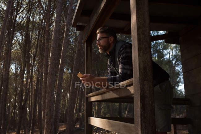 Uomo premuroso con telefono cellulare in piedi al portico cabina — Foto stock