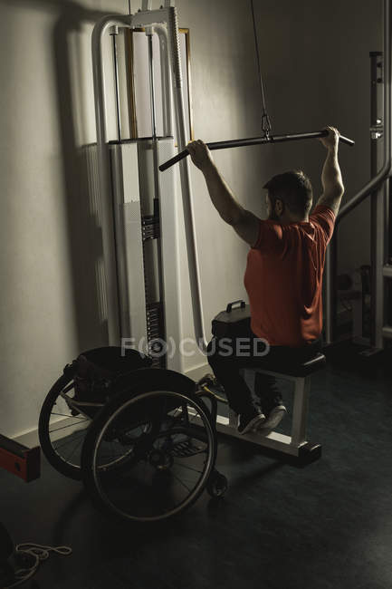 Handicapped man working out lat pulldown training at gym — Stock Photo
