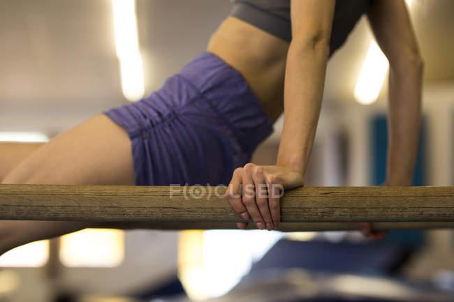 Section médiane de sportive exerçant sur la barre de gym en salle de fitness — Photo de stock