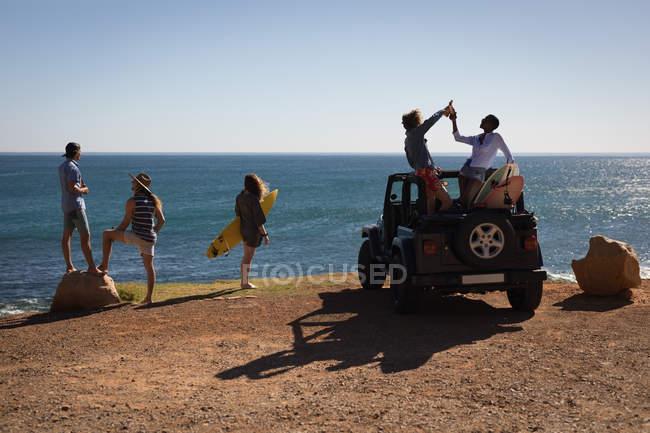 Groupe d'amis, s'amuser à la plage par une journée ensoleillée — Photo de stock