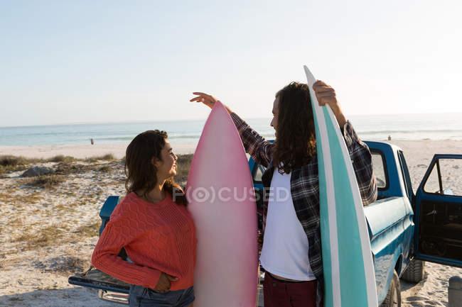 Couple interagissant les uns avec les autres sur la plage par une journée ensoleillée — Photo de stock